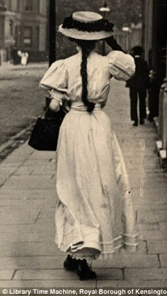 A formally dressed woman in a white dress and a black handbag walks along the street on June 15th 1908