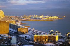 Unusual light conditions over snow-covered Dover Seafront, Kent, England, UK. December 2009 winter panorama of Dover Harbour and Eastern Docks from Western Heights. A2 Jubilee Way, White Cliffs of Dover at East Cliff; Waterloo Crescent, Gateway Flats, Marine Parade, New Bridge, and Beach; A20 Townwall Street and York Street roundabout. Cross-English Channel Ferry Terminal: P and O Ferries, Norfolk Line (now DFDS Seaways), Seafrance; Eastern Arm Pier. See http://www.panoramio.com/photo/303812...