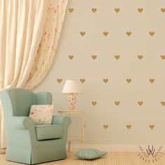Small hazel green little vinyl heart wall decals on a biege wall with a white drape on the left. In front of the wall is a pastel green chair with a white pillow and a small table with a white lamp on top.