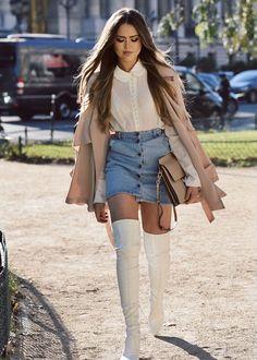 Street style da blogueira Kristina Bazan com saia de botões jeans e botas over the knee branca.