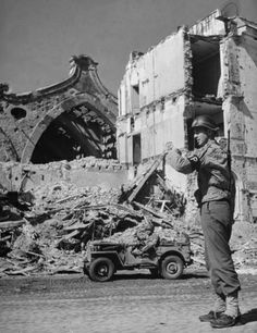 Not published in LIFE. American Military Policeman Ray E. Kellogg directs traffic in bomb-shattered Anzio, 1944.