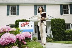 A real estate agent stands in front of a sold house.