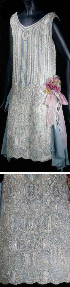 Dress, 1925. Blue silk crepe, embroidered with bugle beads, white and pink iridescent faux pearls, and metallic gold point crochet. Flower on left side of skirt is silk chiffon. Musée Galliera, Musée de la Mode de la Ville de Paris