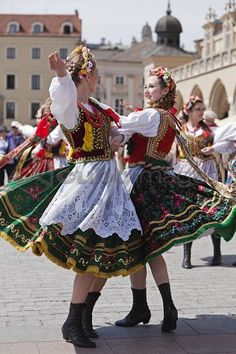 Poland, Cracow. Polish girls in traditional dress dancing in Market Square.