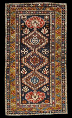 Shirvan rug. Eastern Caucasus, ca. 1880.The navy field displays the characteristic Karagashli pattern of three hexagons each with an outer stepped box edge. At the end of the pole medallion are red sunbursts containing leafy projections. The field also contains ivory crosses and stylized palmettes. The gold main border has the Caucasian slant leaf and chalice design and is flanked by similar guards each in a stylized rosette pattern. This and more important textiles for sale on…