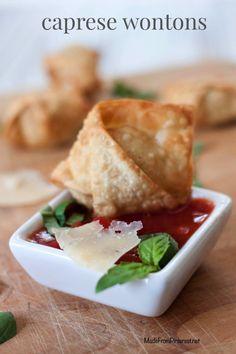 Caprese Wontons - Basil and mozzarella wrapped in a crunchy shell dipped in tomato sauce. A perfect bite.