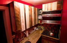 Kitchen with reclaimed wood-covered cupboards and rustic tile in Rufus Wainwright's tiny (400 square feet) Gramercy Park apartment. New York Times, 11/16/12.