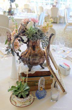 Vintage table scape one of a kind decor from Rent My Dust vintage rentals Romantic Secret Garden Wedding, Silver teapot, pearls perfume bottles, lace, teacups tea party wedding, rentmydust.com succulent