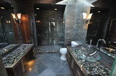 Contemporary Master Bathroom with Glass counters, Handheld showerhead, Wall sconce, Frameless Glass Shower Door, Rain shower