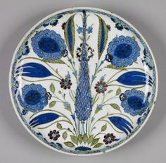 Iznik Fritware Plate Ottoman ceramic artists took much of their inspiration from nature and created designs incorporating stylized leaves with recognizable plants, flowers, and trees. Familiar species depicted on this plate include tulips, and cypress trees. 1525-1550 (Early Modern) fritware with underglaze decoration (Ceramics)