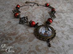Collier couleur bronze orné d'estampes et de perles rouges. Le médaillon central contient un portrait de Bani Thani.