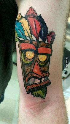 """Aku-Aku """"Oooobadoooga!"""" from Crash Bandicoot tattoo."""