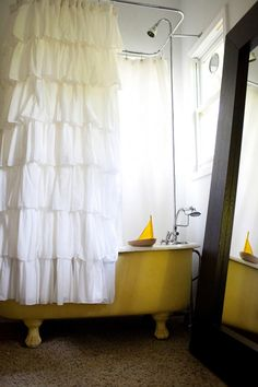 This yellow clawfoot bathtub coupled with the ruffled shower curtain win the award for most charming bathing ensemble, seen via DesignSponge!