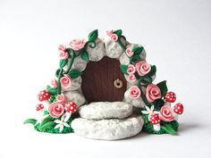 Miniature fairy door with pale pink roses and little toadstools handmade from polymer clay