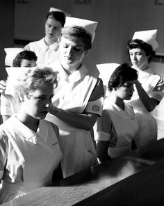 "A group of young 1950s nursing students receiving their caps at graduation. When I went to school we got a cap for ""Capping"" it was a plain white cap, then we got a new cap when we started our 2nd year-it had a yellow stripe. Our 3rd year we got another cap with a blue stripe on it. At graduation we got our 4th cap-with a black stripe on it. We got a total of 4 caps. I'm a proud Diploma grad!"