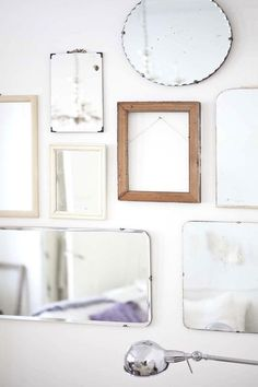 Installing a wall of empty frames and vintage mirrors. This is photographer Mari Eriksson's home.