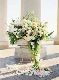 Obviously way too big and extravagant for our wedding, but I love the idea of flowers/greenery dripping down into the petals below. This on a small scale maybe?