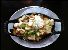 Wood-oven Chilaquiles served in Staub at renowned Chef Rick Bayless' restaurant XOCO in Chicago, IL