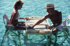 """Slim Aarons Photographic print titled Keep your Cool. Carmen Alvarez enjoying a game of backgammon with Frank """"Brandy"""" Brandstetter in a swimming pool at Acapulco. Available through Framing to a T. Richard Neutra, Kirk Douglas, High Society, Jonathan Adler, Alfred Hitchcock, Ocho Rios Jamaica, Andy Warhol, Palm Springs, Palm Beach"""