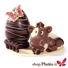 Uovo di pasqua con mucca. È una composizione originale Plusia, azienda che da più di 40 anni produce artigianalmente prodotti dolciari. Realizzazione artigianale con tre tipi diversi di cioccolato e particolari dipinti a mano. Su richiesta realizziamo composizioni personalizzate. Lo puoi comprare su: https://www.plusia.it/shop/c/uova-di-pasqua/