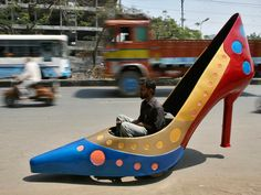 A worker test drives a car in the shape of a heels on a road in the southern Indian city of Hyderabad.