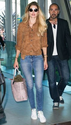 Doutzen Kroes wears a suede shirt and light-wash denim. She pairs the look with round sunglasses, a pink tote and Adidas sneakers.