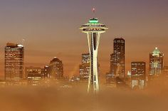 The Seattle skyline rises above an early morning low layer of fog.