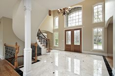 Wood and marble floor foyer with arched staircase, plenty of window rising up two stories #design #nice #foyer