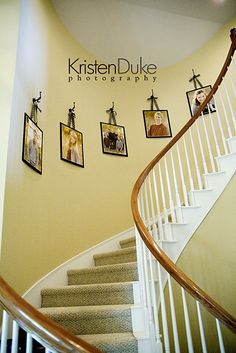 stairway decor... I like the coat hanger hooks with the pictures