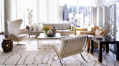 Home Tour: An Airy Manhattan Apartment, Designed to Sell // neutral modern living room with Egg Chair, Barcelona Chair, burl wood stool, leather armchairs, and marble coffee table // living rooms
