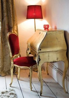 What a beautiful little corner to write a letter...love the red chair and antique ivory desk.