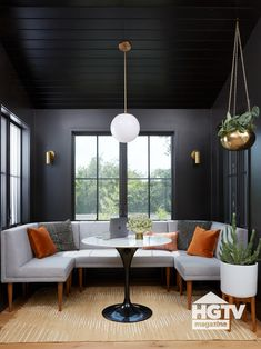 This sleek breakfast nook is painted black and decorated with a U-shaped gray sofa, a hanging globe pendant and patterned pillows. See more on HGTV.com.