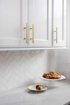 Crisp white cabinets, Super White Quartzite countertops and hand-molded subway tile.  With brilliant brass fixtures and accessories that ramp up the wow factor of this elegant kitchen.