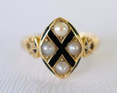"A lovely mourning ring from the 1800's adorned with black enamel and 4 pearls. The enamel formed a ""X"" symbol in the front with 3 grayish and 1 mauve colored pearls set in the north,south,east and west direction of the cross. The border of the diamond panel and the shoulders of the ring has little bit of black enameling work too."