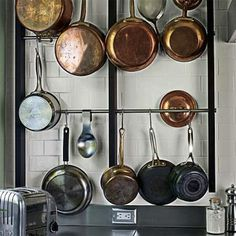Save counter and cupboard space by hanging pots and pans directly on the walls in the kitchen.