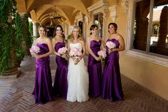 Courtyard picture of bride and bridesmaids with bridesmaids in long purple strapless dresses | villasiena.cc