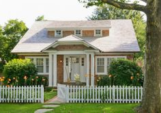 In Good Taste:  Wettling Architects. Charming cedar shake cottage with a a cobblestone path and a white picket fence.