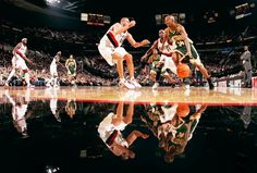 Ray Allen of the Seattle SuperSonics drives on Joel Przybilla and Ruben Patterson of the Portland Trail Blazers on November 30 2004 at the Rose...