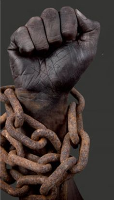 A slave keeping in touch with his african roots by making a fist of black power. As you can see the rusty chains making his arm rusty