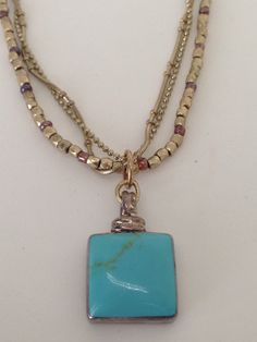 Semi precious turquoise stone pendant adorns this gold tone chain necklace by Bestowed Beads.