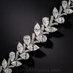 This extraordinary and sumptuous bracelet from the 1950's - 60's, finely crafted platinum, features 24 carats of ultra-sparkling, bright-white, high quality diamonds beautifully arrayed in a gently graduating vine motif, with pear shape and marquise shaped diamonds representing the leaves on the vine. An impressive and important, classic Harry Winston style jewel. A stunning accompaniment to our earrings #20-1-1436. True Golden Age Hollywood glamour!