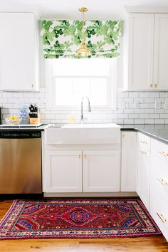 White subway tile as backsplash in white kitchen with leaf patterned curtains and gold light fixture