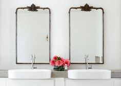 Two vintage style mirrors hang above a concrete counter in a contemporary bath.