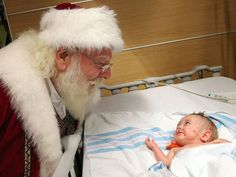 A Macy's Santa Claus visits with 8-month-old Brystal at the hospital