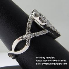 This white gold and diamond wedding ring is one of a kind! It features a bezel set round center diamond and round prong set accent diamond, making it both beautiful and wearable. McNulty Jewelers original design