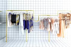 Gold clothes racks in clothing store with floors and walls in the same checkered, black and white print
