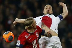 Paris Saint Germain's Zlatan Ibrahimovic (R) fights for the ball with Lille's Simon Kjaer during their French Ligue 1 soccer match at Pierre Mauroy Stadium in Villeneuve d'Ascq May 10, 2014. REUTERS/Pascal Rossignol