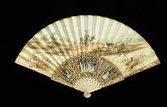 Fan The luminous pastel colors are an outstanding feature of this fan. Typical of fan designs, this one is replete with contrasting imagery.  The elaborate sticks have a decidedly Chinese aesthetic but depict the Three Graces from Greek mythology that represent joy, charm, and beauty.  This imagery in turn contrasts greatly with the pastoral scene of a goat herder.