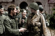 Pvt. James Fergusen of Wortland, Kentucky shakes hands with a German POW following the German defeat at the Battle of Cherbourg. Cherbourg-Octeville, Manche, Normandy, France. 28 June 1944.