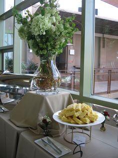 Buffet Table center arrangement. Tall arrangement in glass hurricane. Hydrangeas, greens and curly willow.  Legardia's Flowers & Gifts, Las Vegas, NV. (702) 366-0026.